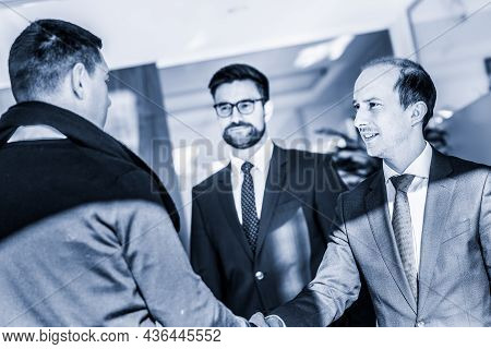 Group Of Confident Business People Greeting With A Handshake At Business Meeting In Modern Office Or