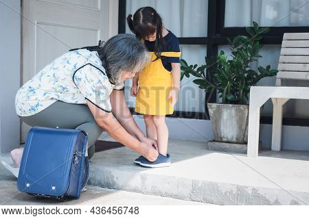 An Elderly Asian Grandmother, Tying Shoelaces For Her 3-year-old Granddaughter, Getting Ready, Befor