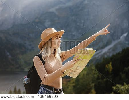 Wanderlust And Travel Concept. Stylish Traveler Girl In Hat Looking At Map, Exploring Woods. Young O