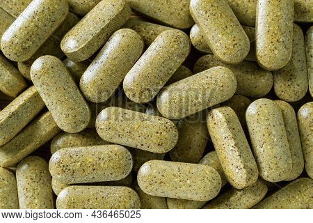 The Everyday Multyvitamin Pills Heap Macro Background. Pile Of Daily Herbal Green Tablets Close-up T