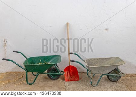 Two Wheelbarrows And Shovel Equipment In Stable At Farm