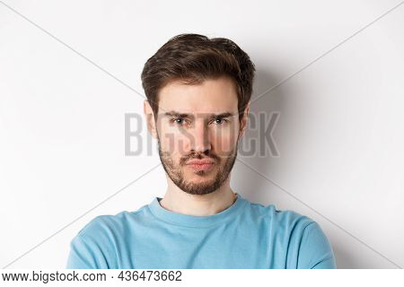 Close-up Of Grumpy Young Man Grimacing, Sulking And Making Offended Face, Standing Upset Over White