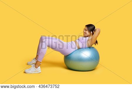 Wellness Concept. Fit African American Lady Doing Abs Exercises On Fitness Ball, Training Over Yello