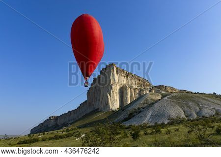 Hot Air Balloon, Red Balloon In The Shape Of A Flying Heart Against The Background Of The White Rock