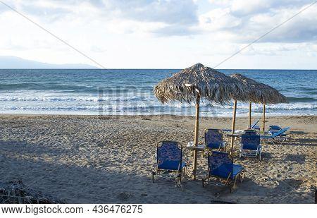 Seaside, Agia Marina, Crete Island, Greece Sun Beds On A Sandy Beach At This Small Greek Resort Near