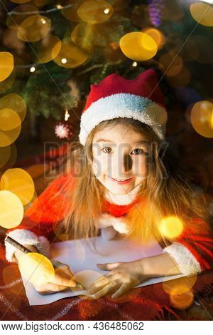 Little Girl In A Santa Hat And Red Dress Under Christmas Tree Is Dreaming, Waiting For The Holiday,