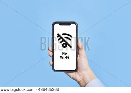 A Person Holds A Mobile Phone With No Wi-fi Symbol On Screen. Hand Holding Smartphone With No Intern