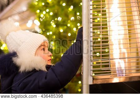 Girl In A Warm Hat Looks At The Flame Of A Gas Burner Warming At A Christmas Market In The City, War