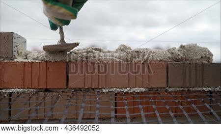 The Master Of The Masonry By The Master Applies Mortar, Cement To The Brick For The Construction Of