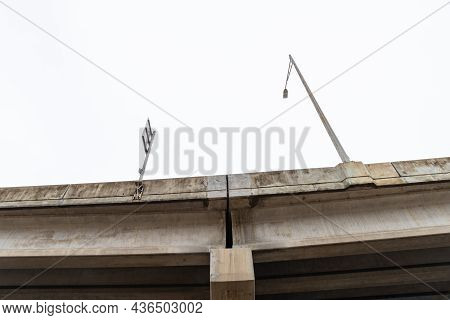 View Looking Up At The Concrete Supports Of An Elevated Roadway Bridge With Light Stanchion And Sign