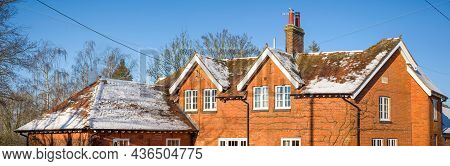 Snow On The Pitched Roof Of A Uk Period House In Winter Time, With Wooden Replacement Double Glazing