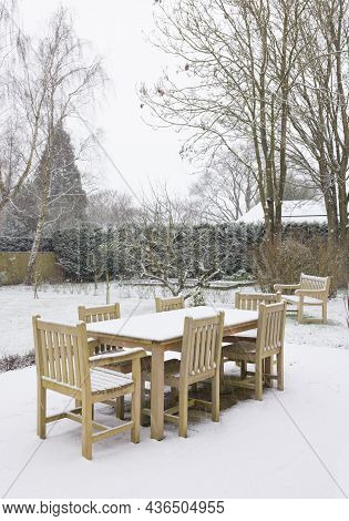 Snow Falling On Garden Patio Furniture In Winter, Uk. Teak Hardwood Wooden Table And Chairs In A Lar