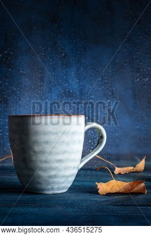 Autumnal Mood. A Cup Of Tea And Autumn Leaves In Front Of A Window With Raindrops