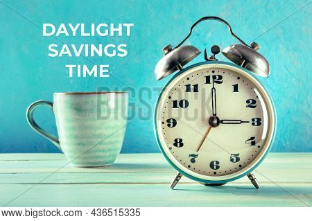 Daylight Saving Time Concept. A Retro Alarm Clock With A Cup Of Coffee On A Teal Background