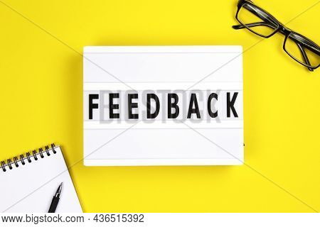 Feedback Word On Lightbox With Eyeglases And Notepad On Yellow Background, Flat Lay