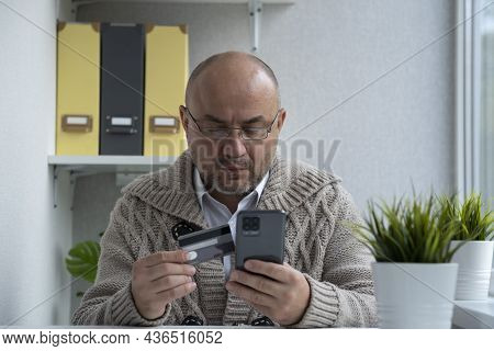 Serious Man Wearing Glasses Paying With Credit Card Online Using Phone. Successful Businessman Makin