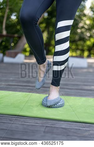 Girl Stands With One Foot On Balancing Disc With Spikes. Impact On The Active Points Of The Foot. Ve