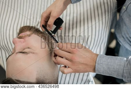 Barber Smooths Clint's Beard With An Electric Razor. The Man In The Barbershop Chair