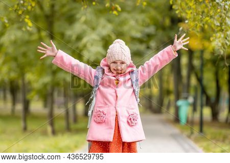 School girl with backpack looking at camera and smiling with hands up at autumn park. Happy preteen child having fun oudoors