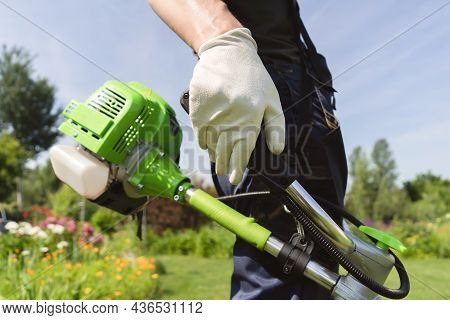 A Close Up Of A Young Man Moving A Lawn With A Lawn Mower In His Hands. A Man Is Caring For His Back