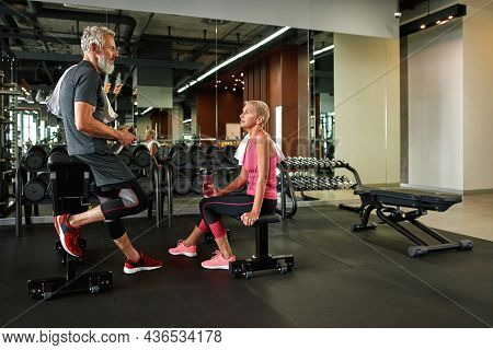 Aged Professional Male Trainer Consulting Attractive Mature Sportswoman In Gym. Experienced Fitness