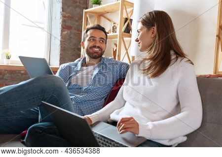 Smiling Married Couple Spending Time Together At Home, Indoors. Middle Aged Couple Sitting Together.