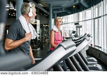 Healthy Cheerful Senior Woman And Man With Towels On Shoulders And White Headphones Running On Tread