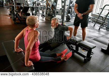 Two Active Senior Man And Woman Working Out In Gym Doing Reverse Push Ups Under Trainers Controll. F