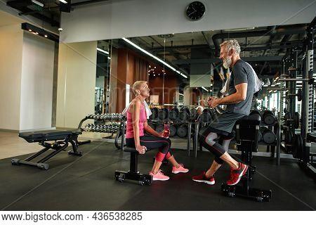 Portrait Of Handsome Elder Gray-bearded Man In Gray Sportswear Standing, Leaning On Gym Equipment, T