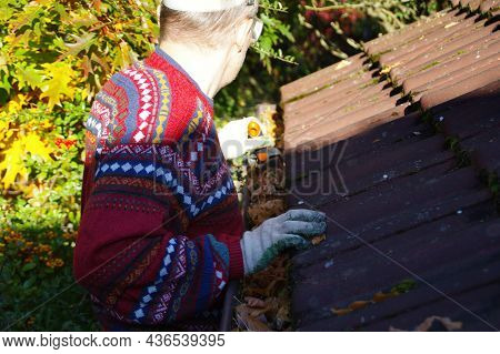 Man Cleaning Roof From Leaves - Gutter Clean In Autumn Season