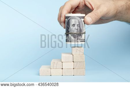 Dollars In Hand On A On Economic Growth On A Blue Background. International Currency And Money Of Th