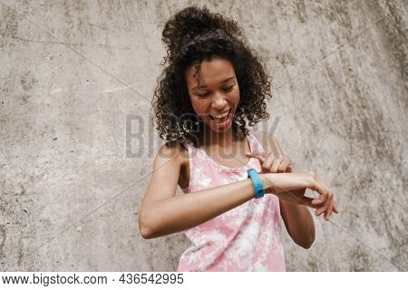Young black sportswoman looking at her smartwatch while standing by concrete wall