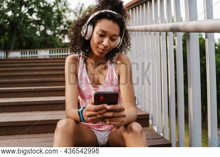 Young black sportswoman in headphones using cellphone while sitting on stairs outdoors