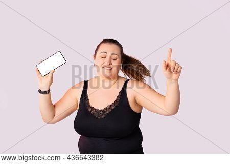 Carefree Overweight, Plus Size Woman Dancing On Crowded Street Listening Music Via Blank Mock Up Whi