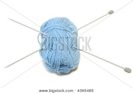 Two Knitting Needles And Woollen Yarn Clew.