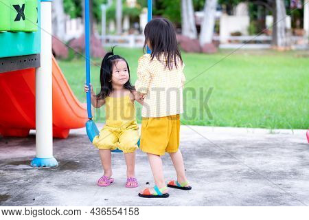 Asian Sibling Girl Playing In The Playground. The Older Sister Stood Talking To The Sister Sitting O