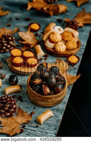 some roasted chestnuts in a wooden bowl and some different confections eaten in Spain on All Saints Day, such as Panellets, Huesos de Santo or Yemas de Santa Teresa on different plates on a gray table