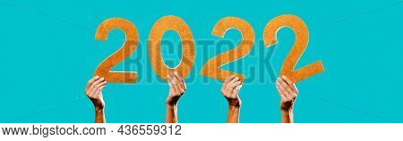 men hands holding four golden three-dimensional numbers forming the number 2022, as the new year, on a blue background, in a panoramic format to use as web banner or header