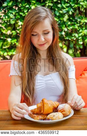 Young Beautiful Woman Enjoy Breakfast In Summer Day. Pretty Girl With Long Hair Eat Fresh Bakery In