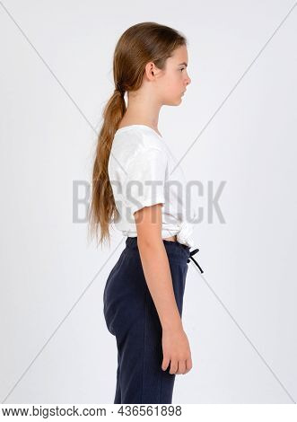 Young Girl In Blue Trousers And White T-shirt Model Snap Right Look Knee High On White Background