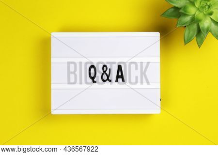 Question And Answer Word On Lightbox With Succulent Flower On Yellow Background, Flat Lay