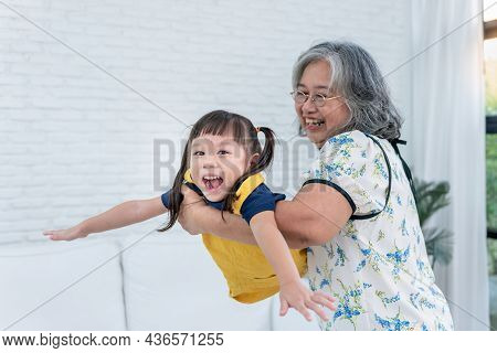 Blurred Soft Images Of Asian Family, 3 Year Old Asian Girl Having Fun And Happy, Imagining Flying, W