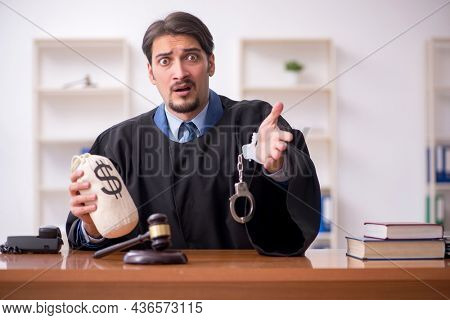Young male judge working in the courtroom
