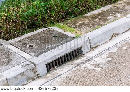 Sewer Drain Along Road. A Storm Drain On The Side Of A Road. Suburban Street Drain.
