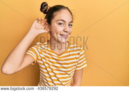 Beautiful brunette little girl wearing casual striped t shirt smiling with hand over ear listening an hearing to rumor or gossip. deafness concept.