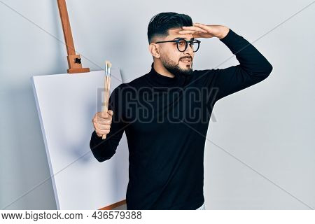 Handsome man with beard holding brushes close to easel stand very happy and smiling looking far away with hand over head. searching concept.