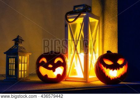 Scary Halloween pumpkins glowing at night as decoration on the front steps