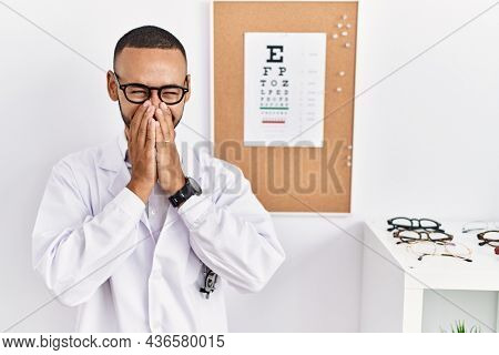 African american optician man standing by eyesight test laughing and embarrassed giggle covering mouth with hands, gossip and scandal concept