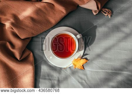 Cup Of Coffee On The Unmade Cozy Bed In Cozy Morning With Sunshine Into Window. Hygge Concept.