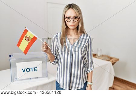 Asian young woman at political campaign election holding spain flag thinking attitude and sober expression looking self confident